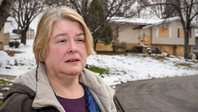 Patti Goke stands near a home along Longview Drive near her home Saturday, Nov. 26, that was recently raided by police and has been condemned twice since July.