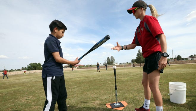 Baseball instructor Courtney Graf shows Jose Diaz how to properly hold the bat during practice Tuesday at Montana Vista Elementary School. The practice was part of Major League Baseball's Reviving Baseball in Inner Cities program.
