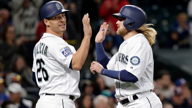 Seattle Mariners' Danny Valencia (left) and Taylor Motter share congratulations after both scored on a single by Ben Gamel against the Texas Rangers in the seventh inning of Saturday's game.