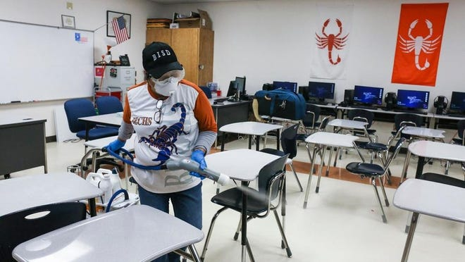 FILE - In this Wednesday, March 11, 2020, file photo, custodial staffer Hortensia Salinas uses an Electrostatic Clorox Sprayer to spray disinfectant in a classroom at Brownsville Early College High School in Brownsville, Texas.