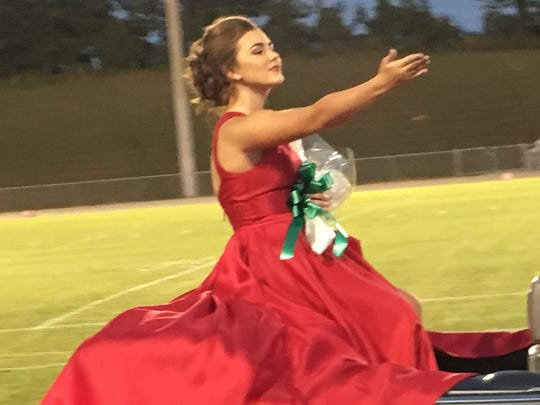 2017 Homecoming Sophomore Attendant Ansley Roper gestures to the cheering crowd prior to the football game at Houston County High School.