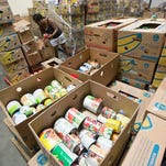 Hornamay Slack sorts through the food donations at the Bay Area Food Bank. The Milton distribution center is rapidly growing and is looking to expand.