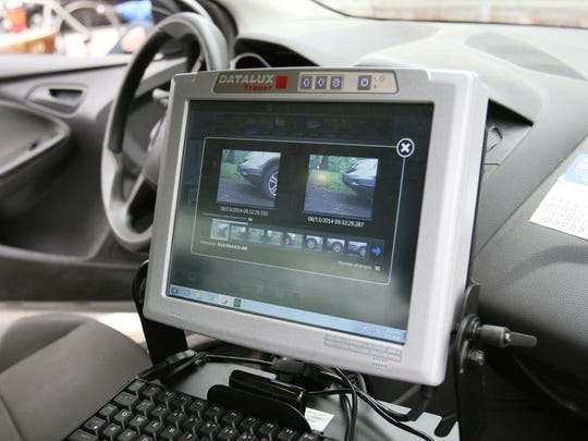 The computer screen in a community service vehicle shows images of a parked vehicles tires taken at two different times and used to determine if it is in violation of time limits on parking.