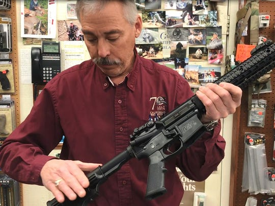 File photo - in December 2017, Rich Howell, manager of Olde West Gun & Loan in Redding, demonstrates the features of an assault weapon under California law. Those features can be modified so the guns don't need to be registered, he said.