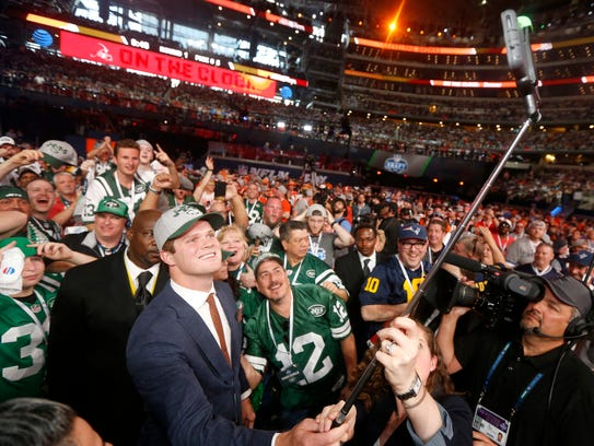USC's Sam Darnold takes a selfie as he poses with fans