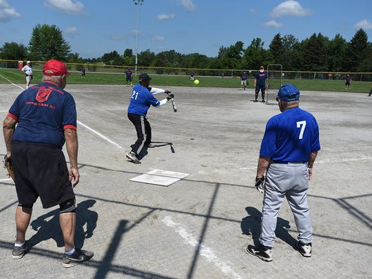 Particpants play some slow-pitch softball in Livonia's 75 and older league on July 17 at Bicentennial Field.