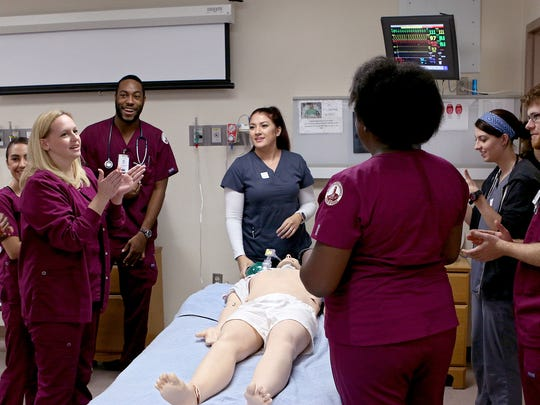 A team of nursing, radiology and respiratory care students at Midwestern State University celebrate the completion of their scenario Friday morning in Bridwell Hall.