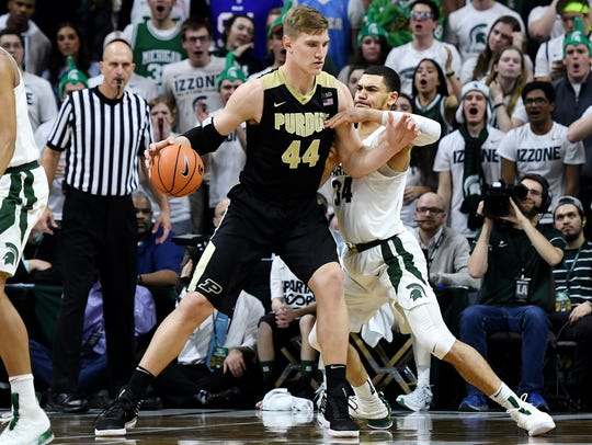 Michigan State's Gavin Schilling, right, guards Purdue's