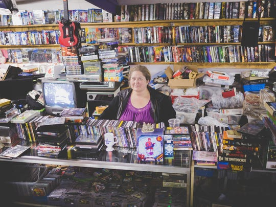 Gina Dill stands in her store, The Movie Zone, at Smiley's Flea Market in Fletcher.