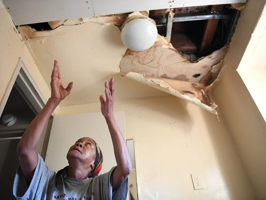 Laura Johnson shows the hole in the ceiling of her daughter's apartment at Pueblo City Apartments in Newark. Johnson said the ceiling has collapsed multiple times, nearly hitting her.