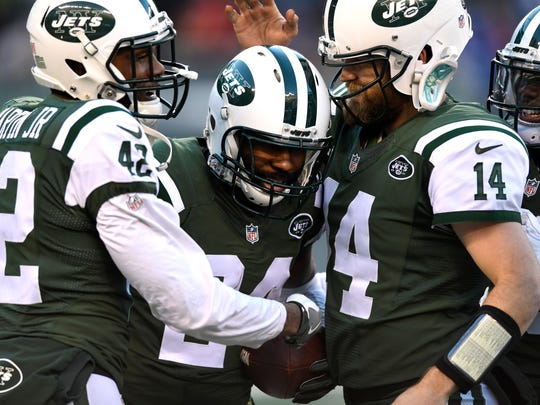 New York Jets cornerback Darrelle Revis (24) celebrating with strong safety Ronald Martin (42) and quarterback Ryan Fitzpatrick after his inteception in the fourth quarter.