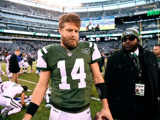 New York Jets quarterback Ryan Fitzpatrick (14) walks off the field after what could be his last game in the Jets uniform.