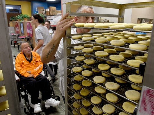 John Rose rolls a tray of donuts into the oven at Dippin' Donuts Thursday, Jan. 12, 2017 under the supervision of Labib Sayar in the wheelchair. Sayar is friend and former business partner of Kent Tharp. Tharp has moved his family operated business to a news location on Maynardville Pike in Halls.
