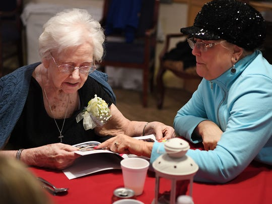 Cecelia Barry and her niece, Janet Chester of Mahwah, look through a book of photos taken at a party for her 100th birthday, which was celebrated at Woodcrest.