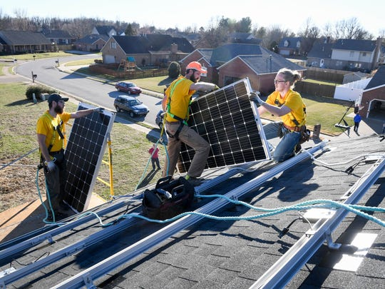 Solar panel installers (L-R) Corey Kimball, Ryan Zaricki and Eli Metzler-Prieb place new panels on the roof of a home on Eau Claire Lane in Newburgh in February 2017. A new Indiana senate bill will reverse a 2017 law that reduced over time the value of privately generated solar power in Indiana.