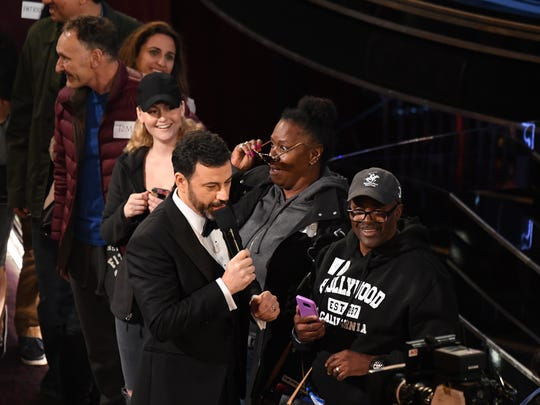 Jimmy Kimmel gives a pair of Jennifer Aniston's sunglasses to a woman who is part of a group of tourists from a bus tour at the Academy Awards:.