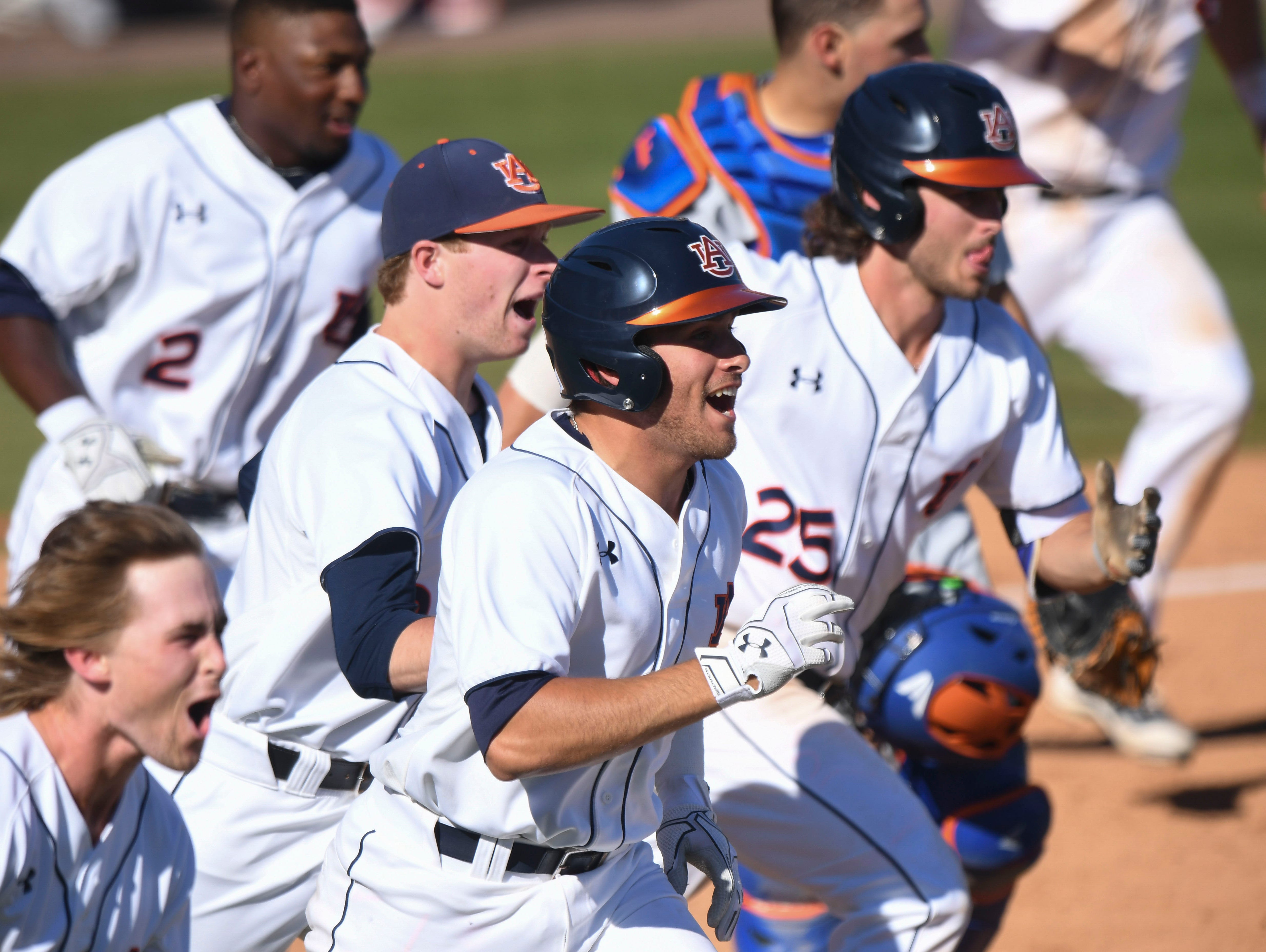 Auburn baseball players celebrate the walk-off win vs Florida to complete the three-game sweep on Sunday, March 19, 2017 in Auburn, Ala.