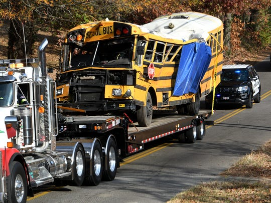 In this file photo, Chattanooga Police vehicles escort a flatbed truck hauling a crushed school bus from the scene on Talley Road in Chattanooga. Six Woodmore Elementary School students were killed and several others were injured when the bus crashed.