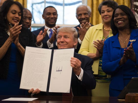 President Donald Trump (center) holds up an executive order to bolster historically black colleges and universities after signing it in the Oval Office of the White House in Washington, on Feb. 28, 2017.
