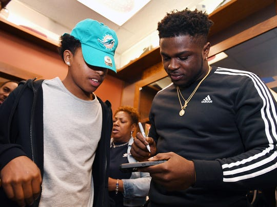 (right) Jabrill Peppers, former Paramus Catholic football star who will soon be drafted into the NFL, signs a cell phone for (left) Devon Virgil, at Packer Shoes in Teaneck on Saturday, April 22, 2017.