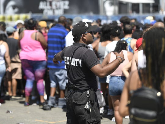 Security directs concert goers waiting in line outside