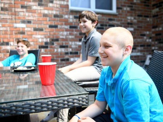 Bennett Burgida, 10, far right, with his brothers Aidan, center, and Max, left, laugh as they talk about how much money they raised for Tackle Kids Cancer Fund at HackensackUMC. When Bennett was diagnosed with non-Hodgkin's lymphoma in February, his brothers decided to raise money to buy him gifts to lift his spirits. But $30,000 dollars later, they decide to donate it for cancer research.