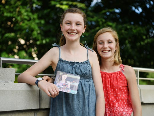 Lillian Chase, 12, holds her first album with sister