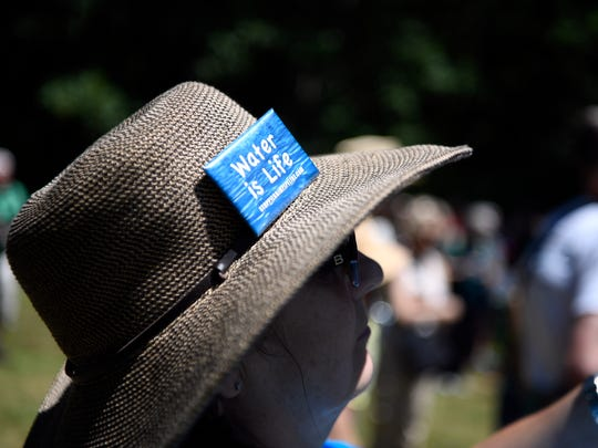 """Catherine Kraft of Glen Rock wears a pin that reads """"Water is Life,"""" during the rally protesting the Pilgrim Pipelines near the Ramapo Reservation in Mahwah on Sunday."""