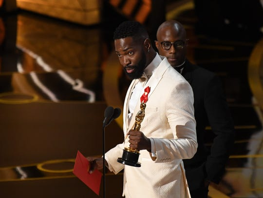 Tarell Alvin McCraney, left, and Barry Jenkins accept