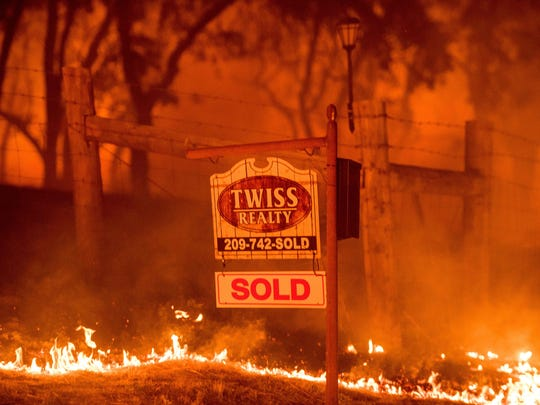 TOPSHOT - A real estate sign is surrounded by flames