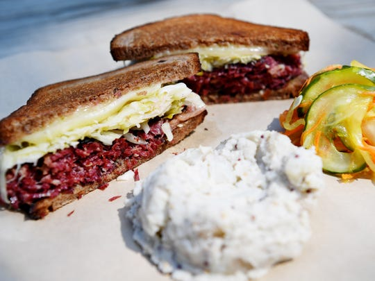 Rise Above Deli's pastrami Reuben made with house made rye sourdough, sauerkraut, special sauce and swiss with a side of smoked potato salad with smoked potatoes, celery, house mayo and mustard.