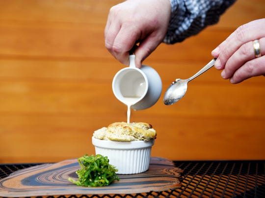 Jargon owner Sean Piper pours a creamy broth into a cup of mussel soufflé with seafood essence.