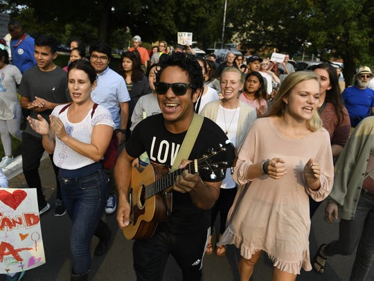Gustavo Guerrero marches with a guitar during a rally