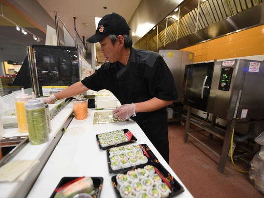 A sushi chef working at the newly remodeled Stop &