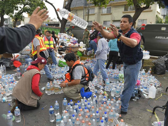 Volunteers distribute water and other donated beverages