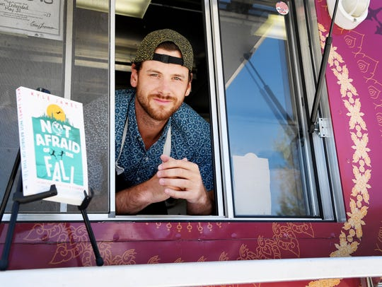 Author Kyle James stands at the window of his food
