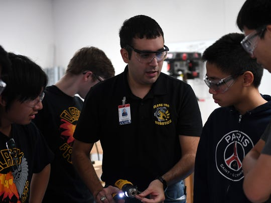 Capt. Victor, 17th Attack Squadron MQ-9 Reaper pilot, shows a high school robotics team how to work with an electric drill, in Las Vegas, Sept. 7, 2017. Victor volunteers as a mentor for a local high school robotics team during his days off in hopes of inspiring the youth to follow their aspirations to the highest degree.