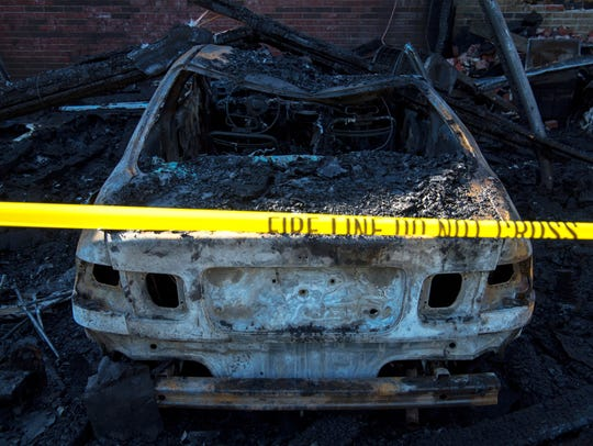 One of three charred vehicles is parked on the backside