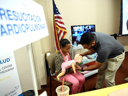 """Holy Name Medical Center staff Giuseppe Defenza shows Daniela, 9, of Hackensack, how to apply CPR to a choking baby during the """"Familia y Salud"""" health fair on Saturday."""