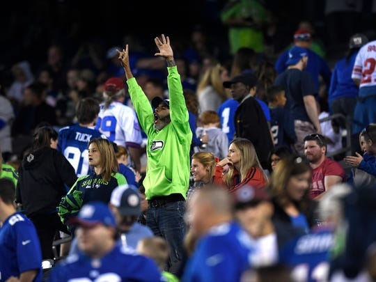 A Seahawks fan cheers as Giants fans leave the stadium in the fourth quarter. The Seattle Seahawks defeat the New York Giants 24-7 on Sunday, October 22, 2017 in East Rutherford, NJ.