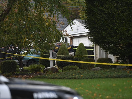 Bergen County sheriff's officers put up a barrier to block the view of the side of  a home at Spring Valley Road and Brookfield Avenue in Paramus, where a body was found after an apparent homicide on Tuesday, Oct. 24.