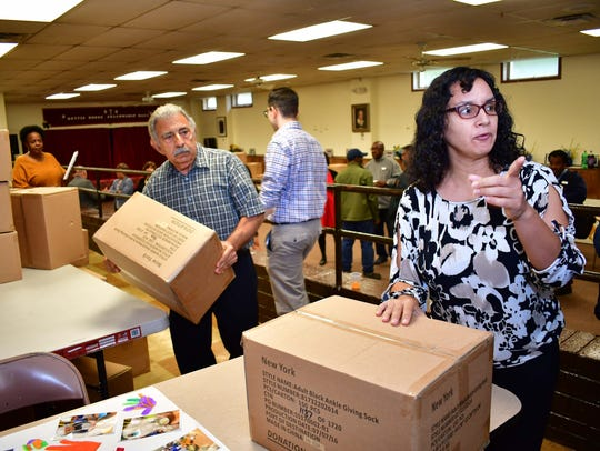 Bloomfield Councilman Nick Joanow, left, carries a box at left while Sonia Mulero, social work specialist, right, points. New socks from Knock Knock a Sock were distributed to organizations serving the homeless and low-income populations at the New Light Baptist Church on Dewey Street in Bloomfield on Wednesday, Oct. 25.