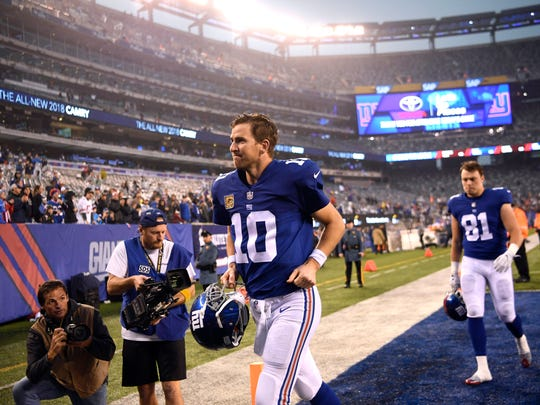 New York Giants quarterback Eli Manning (10) walks