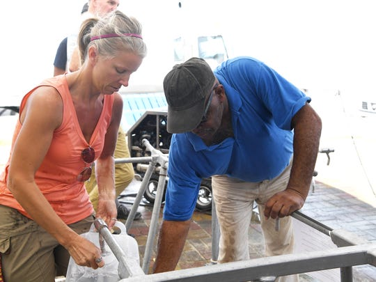 Leah Wilson, of Minnesota, helps Mackenzie Frank fill a water jug in Barbuda November 7, 2017. Wilson traveled to the hurricane devastated island to volunteer after spending vacations there.