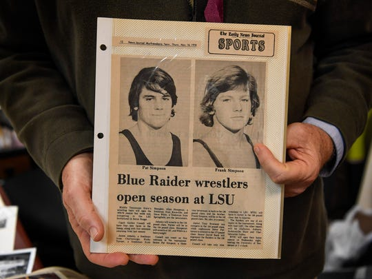 Coach Frank Simpson holds a newspaper article from his scrapbook of when he and his brother Patrick wrestled at Middle Tennessee State University.