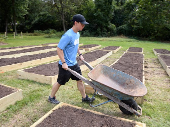 Volunteer Jonathan Lee moves wheelbarrow used to fill raised planting beds at Sow Reap Feed's new Jackson micro farm.