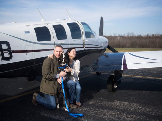 Five-month-old boxer Sophia poses for a pre-flight photo with Scott and Jackie Evans. The Evans flew their plane to Island Home Airport in Knoxviille, Tenn., Saturday, Dec. 16 to pick up Sophia who suffers from severe anxiety. They'll take her to South Carolina to work with a dog behaviorist. When her treatment is over, the dog will return to Knoxville where East Tennessee Boxer Rescue will work to find her a forever home.