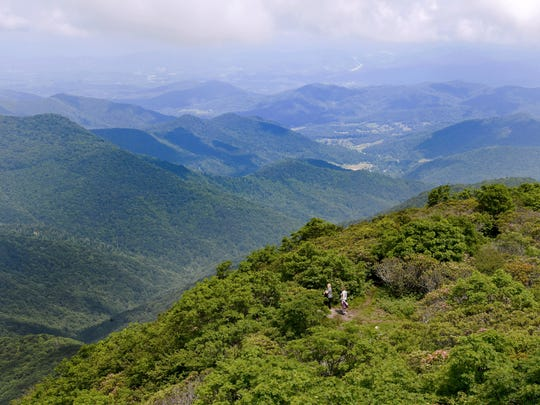 A pair of hikers make their way up to the Craggy Pinnacle at Craggy Gardens on the Blue Ridge Parkway on Thursday, June 15, 2017.