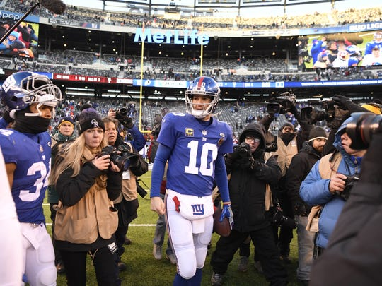 New York Giants quarterback Eli Manning (10) is surrounded