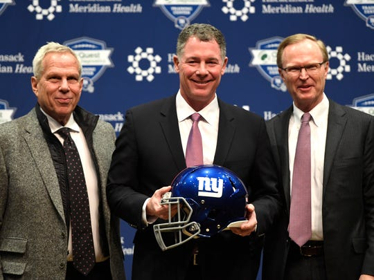 New Giants head coach Pat Shurmur, center, poses for photos with owners Steve Tisch, far left, and John Mara, far right.